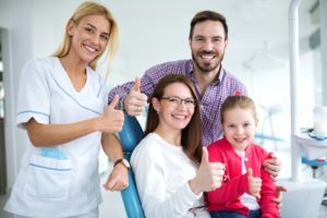 a dentist and a family with a young daughter smiling and giving a thumbs up during a visit