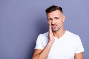 Man in dental pain with hand on side of face