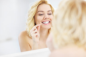 Woman flossing teeth in mirror