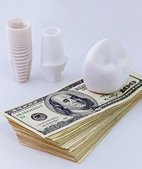 A dental crown and implant in Carrollton and a stack of money