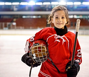 a child posing in a hockey uniform on an ice rink