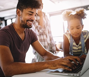 a smiling person searching on their laptop with their child looking